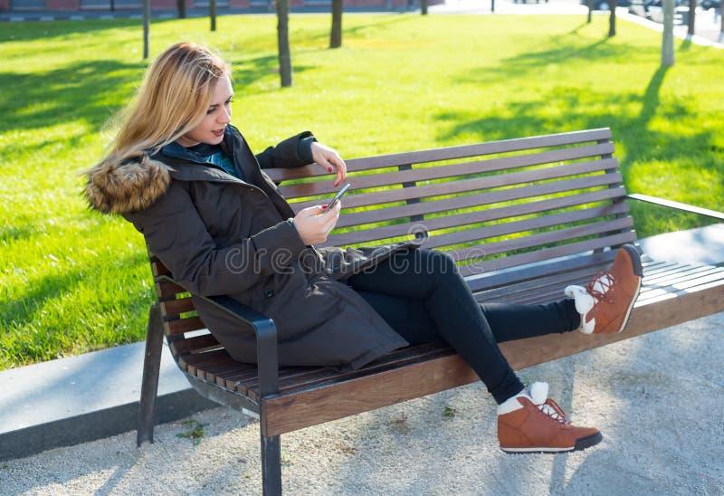 Młodej kobiety obsiadanie na ławce, jesień zdjęcia royalty free