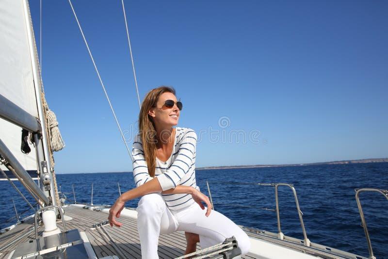 Młodej kobiety obsiadanie na żeglowanie łodzi obrazy stock