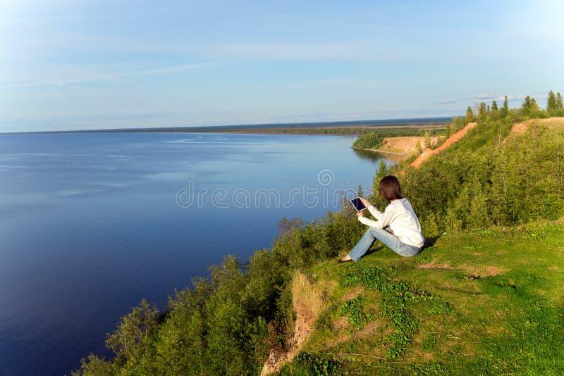Młodej kobiety obsiadanie na brzeg jezioro z pastylką oblicza fotografia stock