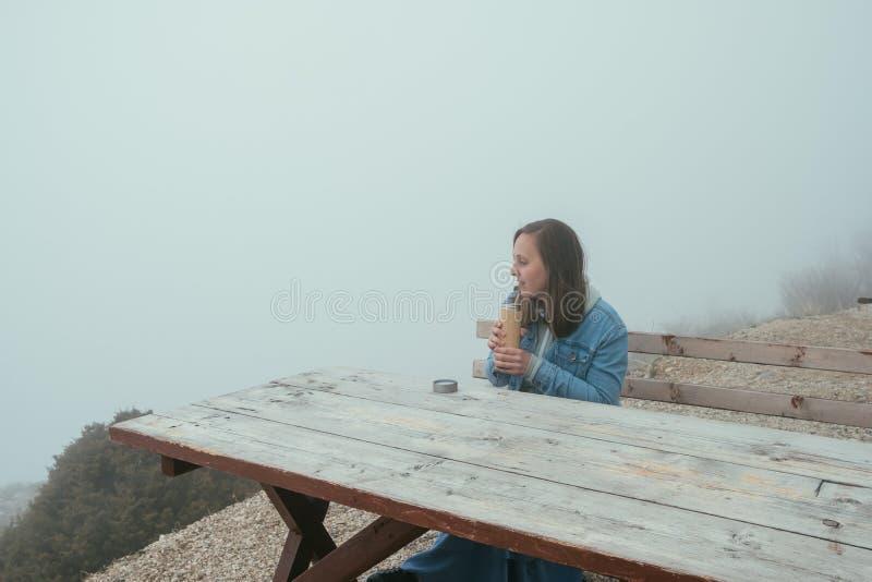 Młodej kobiety obsiadanie na Drewnianej ławce i pić gorącej herbaty od a zdjęcie stock