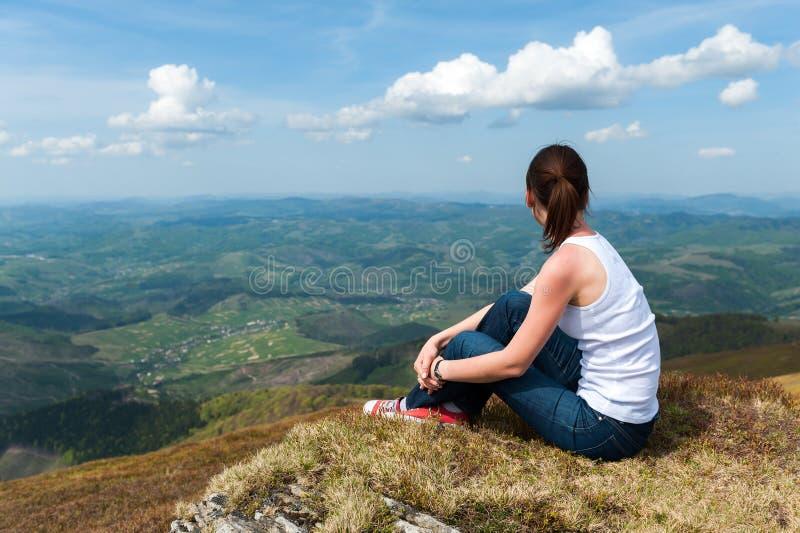 Młodej kobiety obsiadanie na górze góry i patrzeć ziemię zdjęcie stock