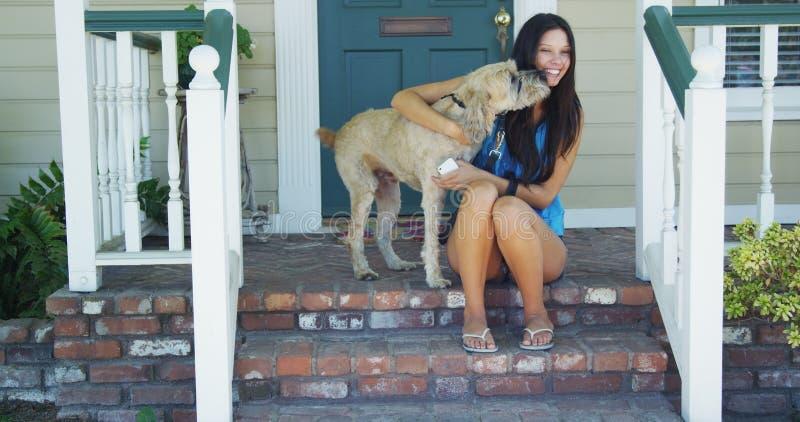 Młodej kobiety obsiadanie na ganeczku z jej psem obrazy stock