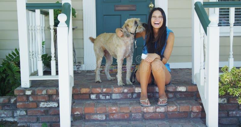 Młodej kobiety obsiadanie na ganeczku z jej psem zdjęcie royalty free