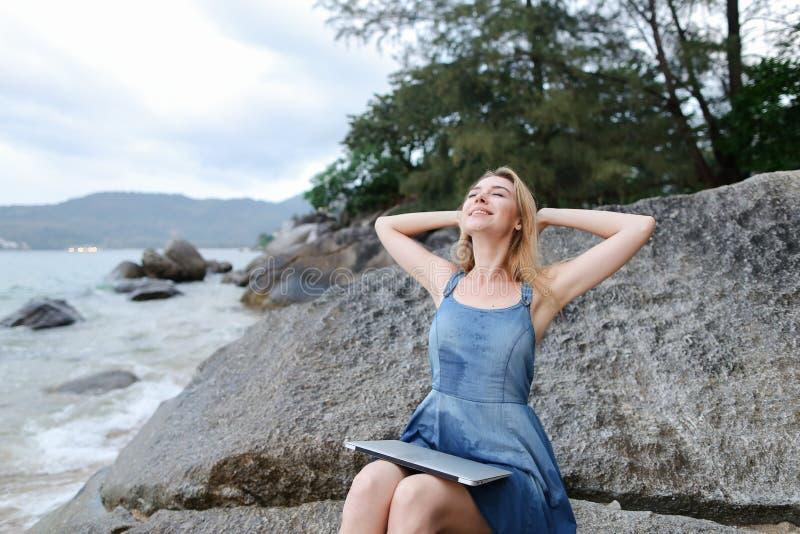 Młodej kobiety obsiadanie na kamieniach z, pustym dennym brzeg i plaży zamkniętym laptopem i podnosić rękami, fotografia stock