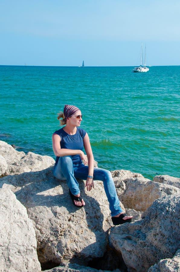 Młodej kobiety obsiadanie na kamieniu na seashore zdjęcia royalty free