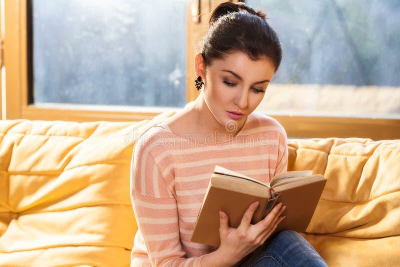 Młodej kobiety obsiadanie na leżance w domu i czytający książkę zdjęcie royalty free