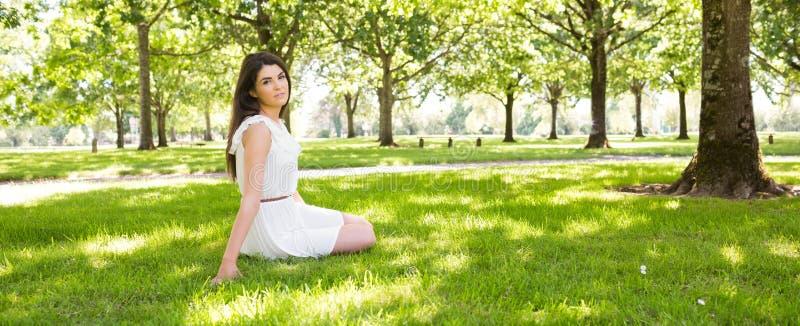 Młodej kobiety obsiadanie na obszarze trawiastym w parku zdjęcie stock