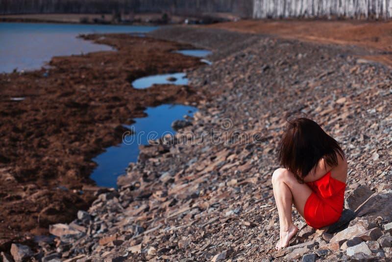 Młodej kobiety obsiadanie na plaży w czerwonej sukni obrazy stock