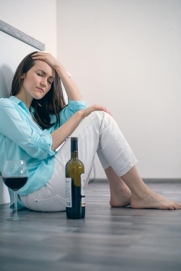 Młodej kobiety obsiadanie na podłogowym pije winie, alkoholizm, depresja, rozwód obraz stock