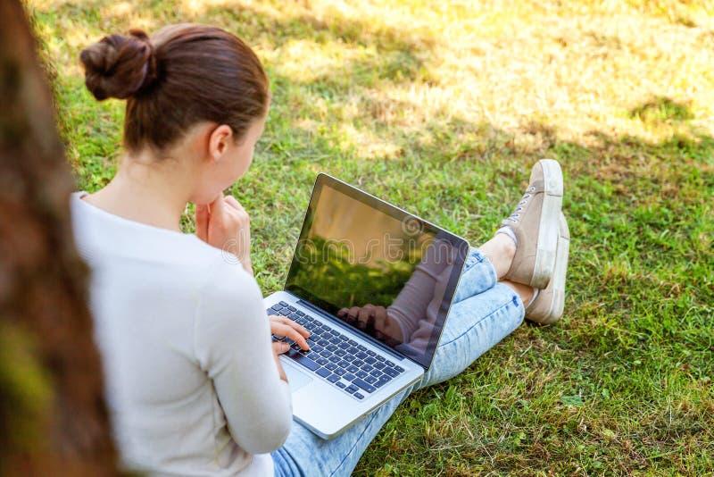 Młodej kobiety obsiadanie na zielonej trawy gazonie w miasto parku pracuje na laptopu komputeru osobistego komputerze Freelance b zdjęcia stock