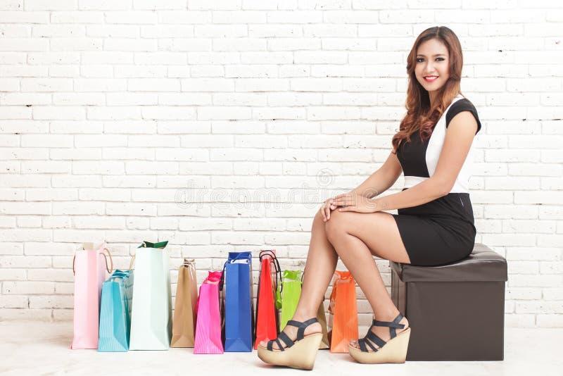 Młodej kobiety obsiadanie obok multicolor torba na zakupy obrazy stock