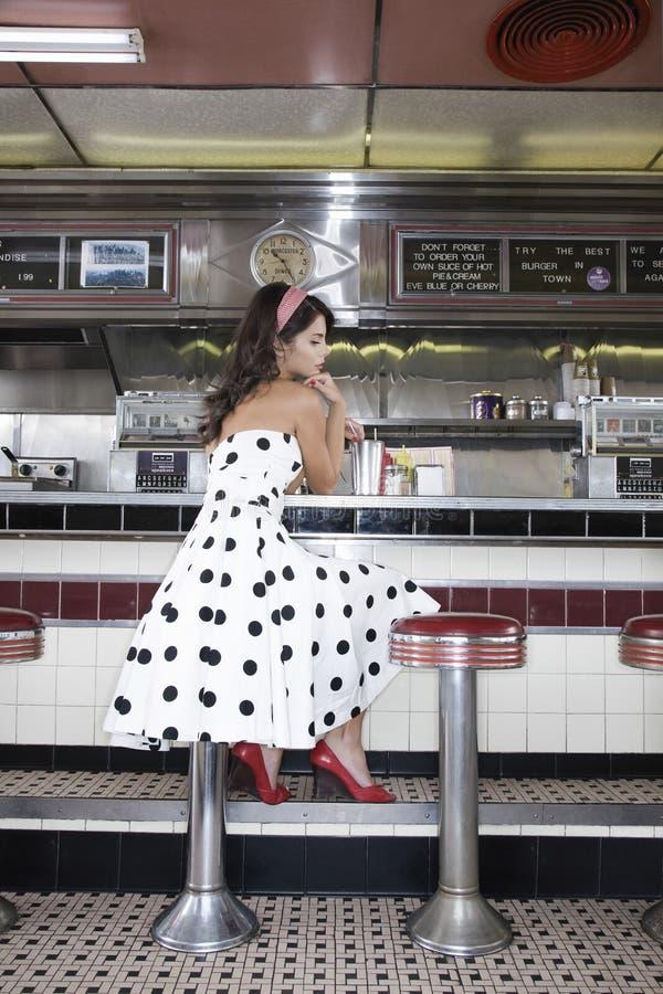 Młodej Kobiety obsiadanie Przy gościa restauracji kontuarem zdjęcia stock