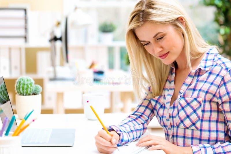 Młodej kobiety obsiadanie przy jej biurkiem obraz royalty free