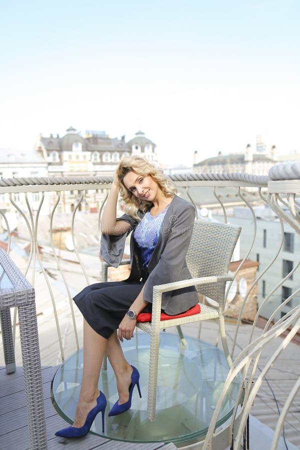 Młodej kobiety obsiadanie przy kawiarnią na balkonie z pejzażu miejskiego tłem zdjęcie royalty free