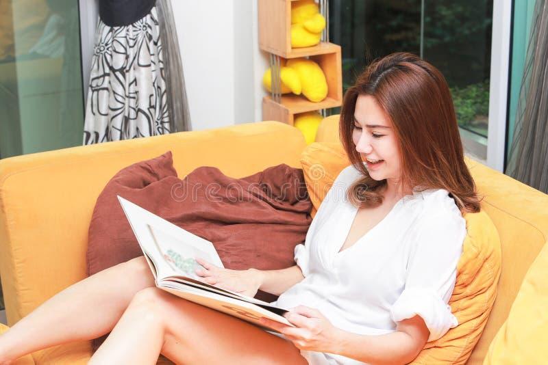 Młodej kobiety obsiadanie przy rozpieczętowanym nadokiennym czytaniem książka cieszy się ponowny obrazy royalty free