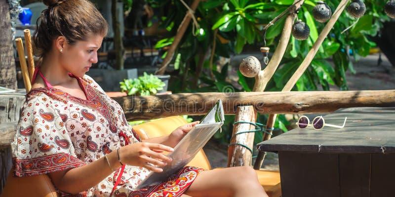 Młodej kobiety obsiadanie w bambus plaży barze, patrzeje menu obrazy royalty free