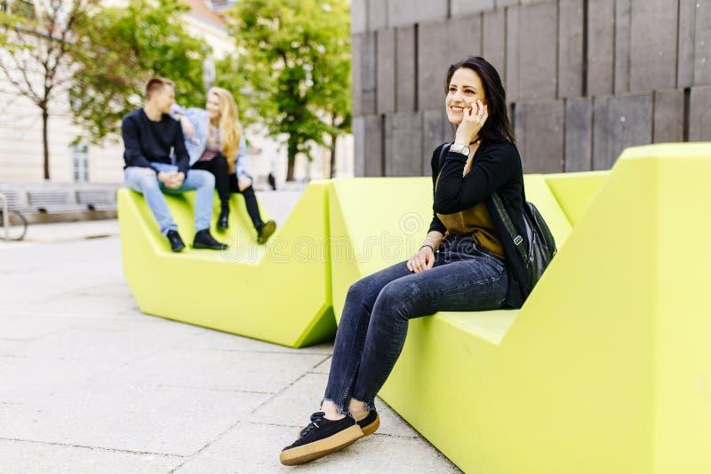 Młodej kobiety obsiadanie w mieście i używa telefon komórkowego zdjęcie stock