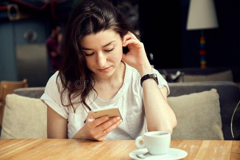 Młodej kobiety obsiadanie w sklep z kawą przy drewnianym stołem, pić kawowy i używać smartphone, zdjęcia stock