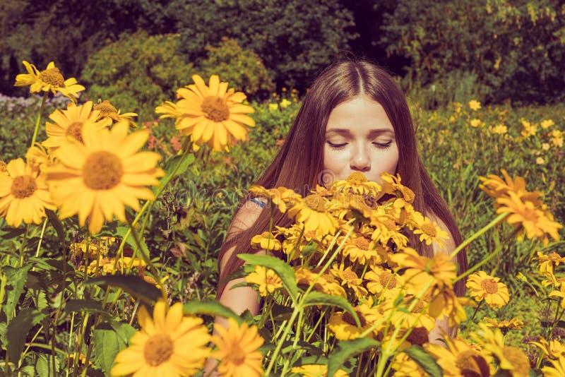 Download Młodej Kobiety Obwąchanie Kwitnie Heliopsis W Ogródzie Fotografia Tonująca Obraz Stock - Obraz złożonej z flirt, zrozumienie: 53784939