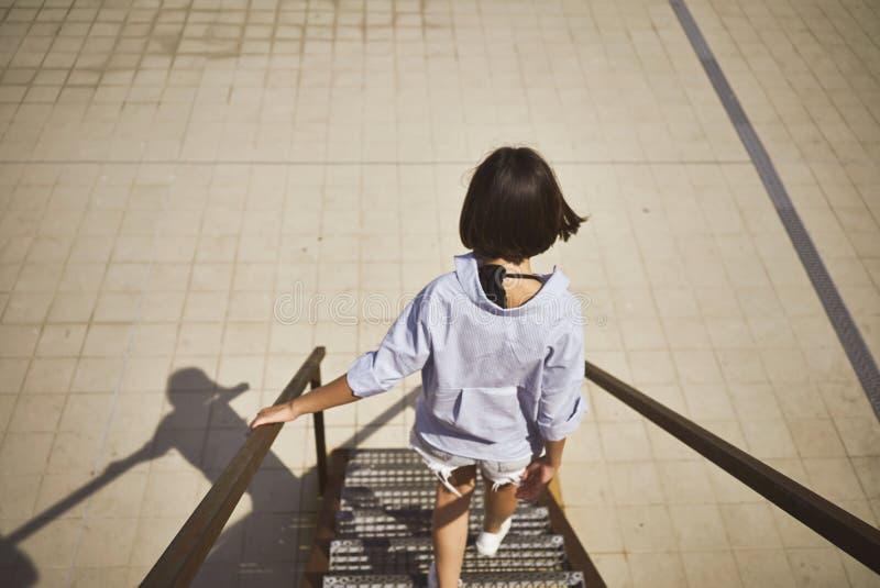 Młodej kobiety odprowadzenia puszek schodki zdjęcia stock