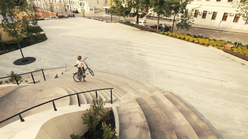 Młodej kobiety odprowadzenia puszka rowerowi schodki i mienie jego wręczają bicykl zdjęcie stock