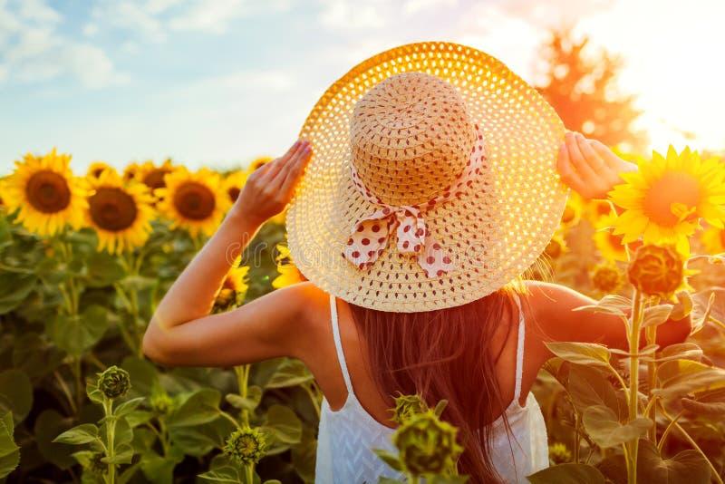 Młodej kobiety odprowadzenie w kwitnącym słonecznika polu trzyma słomianego kapelusz katya lata terytorium krasnodar wakacje zdjęcie royalty free