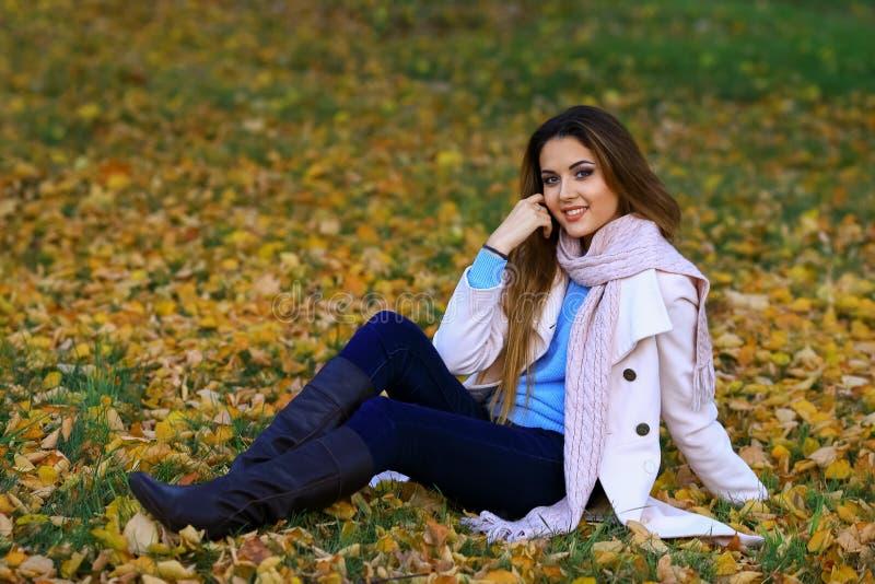 Młodej kobiety ono uśmiecha się i spadku klonu ogródu żółty tło wolna przestrzeń zdjęcie stock