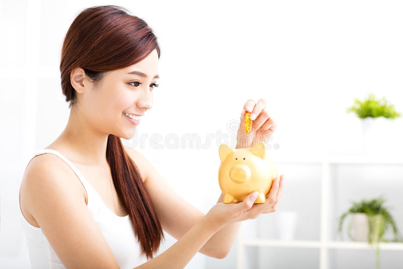 młodej kobiety oszczędzania pieniądze w prosiątko banku zdjęcie royalty free