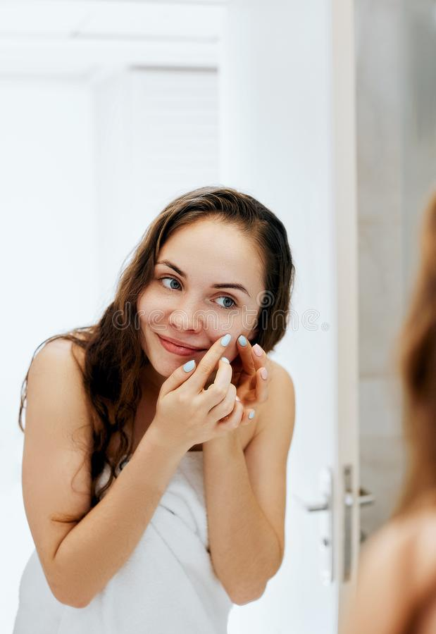 Młodej kobiety patrzeć i ściśnięcie trądzik na twarzy przed lustrem Brzydka problemowa skóry dziewczyna, nastoletnia dziewczyna m obraz royalty free