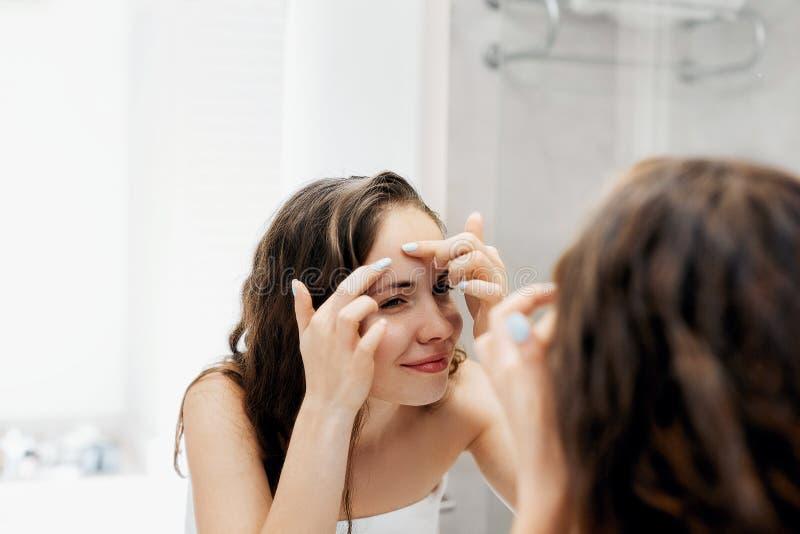 Młodej kobiety patrzeć i ściśnięcie trądzik na twarzy przed lustrem zdjęcia stock