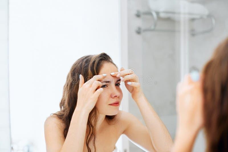 Młodej kobiety patrzeć i ściśnięcie trądzik na twarzy przed lustrem obraz stock