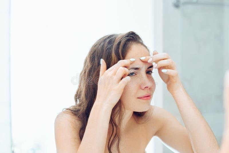 Młodej kobiety patrzeć i ściśnięcie trądzik na twarzy przed lustrem Brzydka problemowa skóry dziewczyna, nastoletnia dziewczyna m fotografia stock