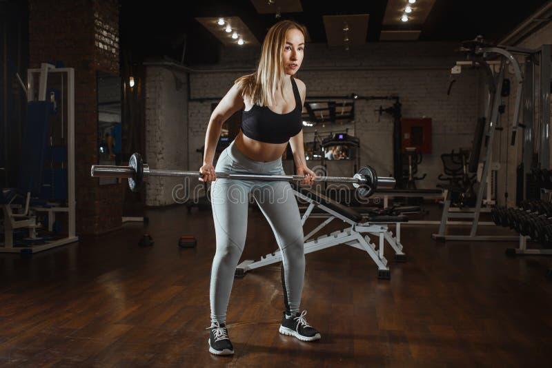 Młodej kobiety podnośny barbell z światło ciężarami przy gym Sprawności fizycznej crossfit żeński robi trening zdjęcia royalty free