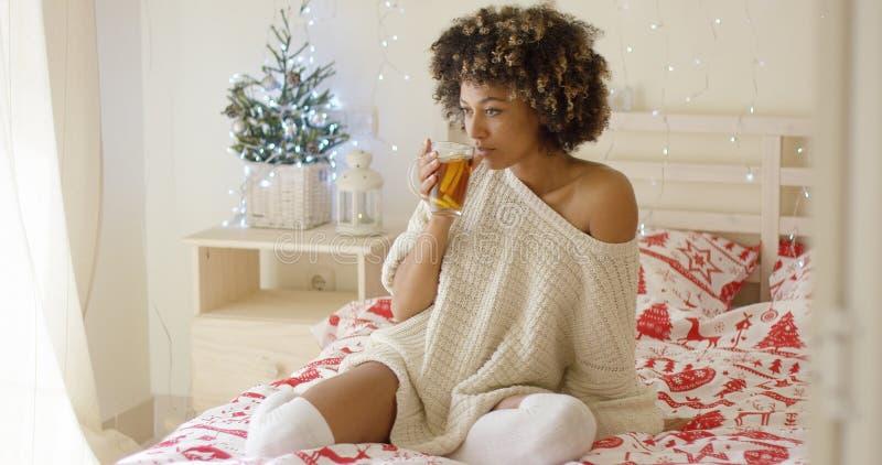 Młodej kobiety popijania herbata podczas gdy sadzający w łóżku fotografia stock