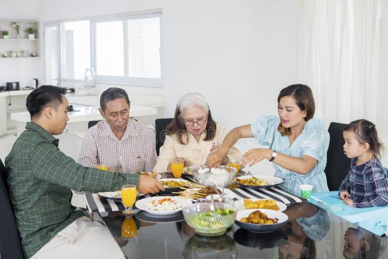 Młodej kobiety porcji foods dla jej dużej rodziny zdjęcie stock