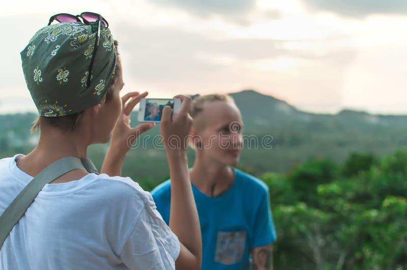 Młodej kobiety pozycja bierze obrazek zmierzchu krajobraz zdjęcia royalty free