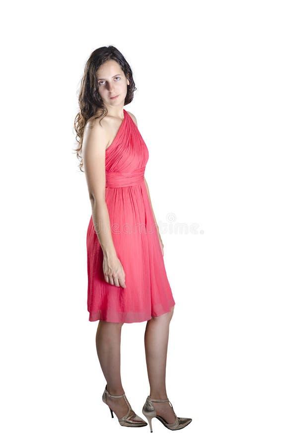 Młodej kobiety pozycja jest ubranym koralowe smokingowe i złociste szpilki obraz royalty free