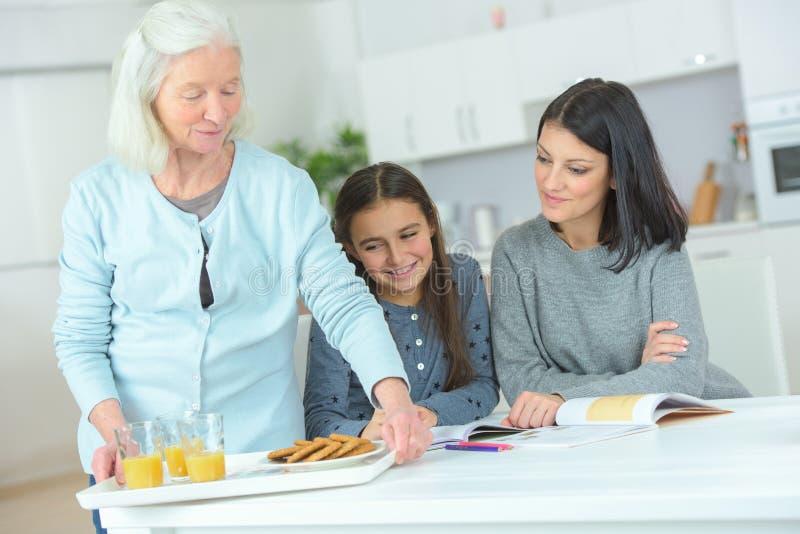 Młodej kobiety pozycja obok matki i babci w kuchni fotografia royalty free