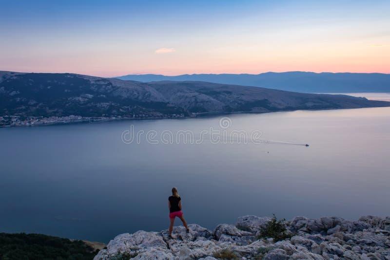 Młodej kobiety pozycja przy skałą, patrzejący wschód słońca i morze fotografia royalty free