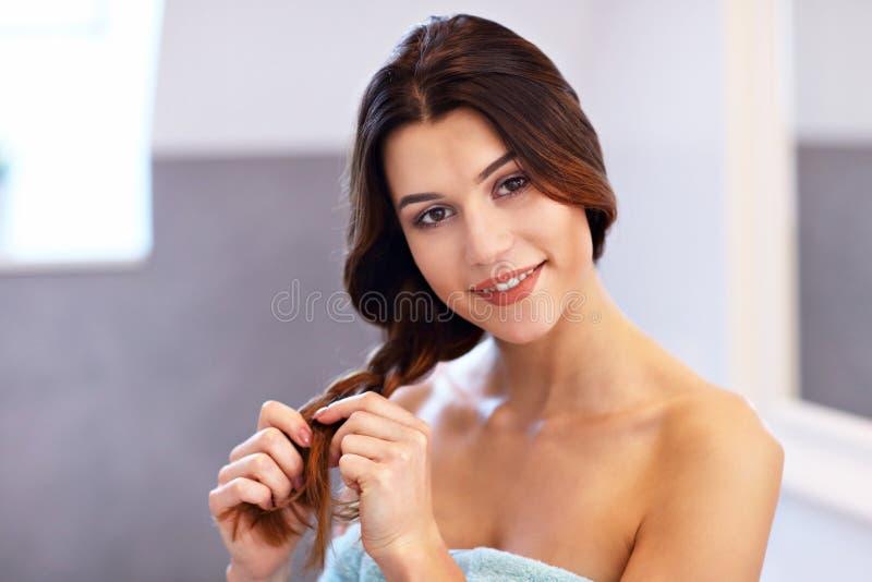 Młodej kobiety pozycja w łazience i szczotkować włosy obrazy royalty free