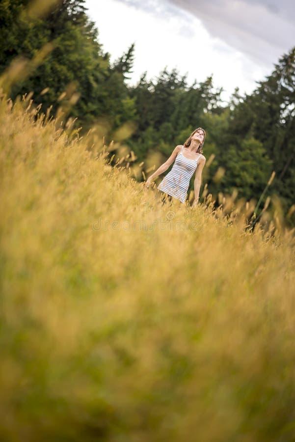 Młodej kobiety pozycja w jesieni łąkowy przyglądającym up w niebie zdjęcia stock