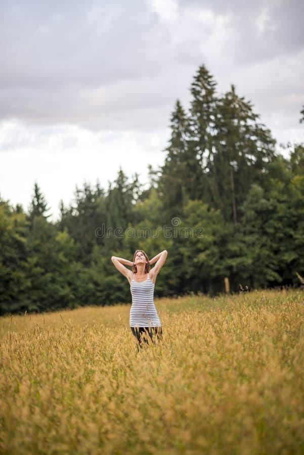 Młodej kobiety pozycja w jesieni polu z wysoką trawą zdjęcia royalty free