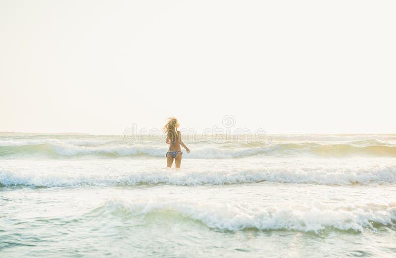 Młodej kobiety pozycja w wodach morze śródziemnomorskie, Rhodes obraz stock
