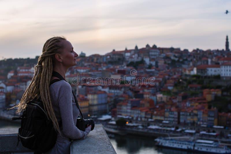 Młodej kobiety pozycja z kamerą w starym miasteczku podczas półmroku, Porto, Portugalia obrazy royalty free