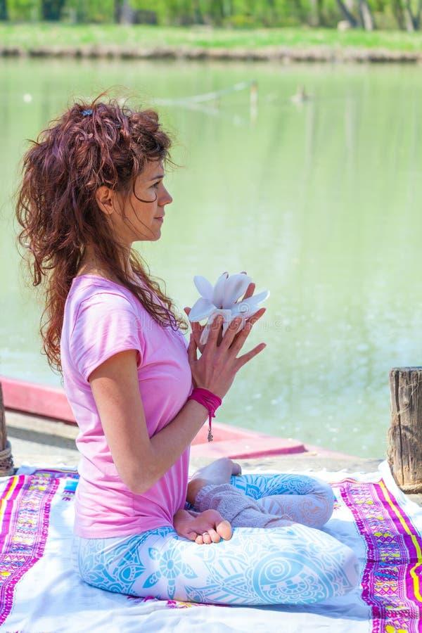 Młodej kobiety praktyki joga plenerowy jeziornego chwyta magnoliowego kwiatu styl życia zdrowym pojęciem obraz royalty free