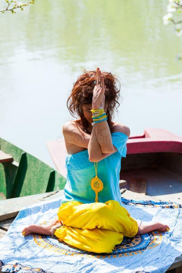 Młodej kobiety praktyki joga plenerowy jeziornym zdrowym styl życia pojęciem folował ciało strzału letniego dzień obrazy stock
