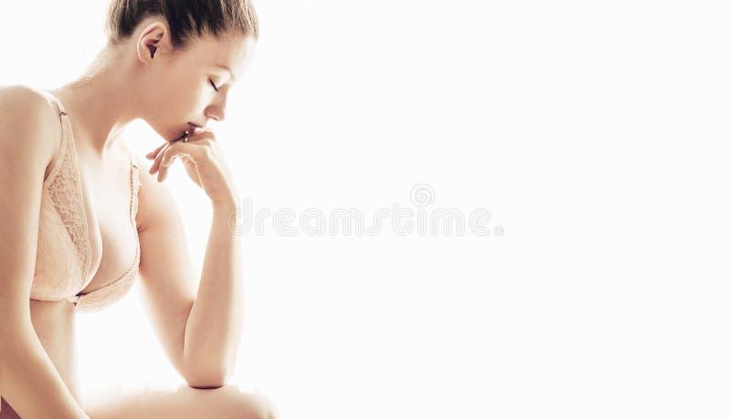 Młodej kobiety przyglądający zmęczony odosobniony na białym tle zdjęcia stock