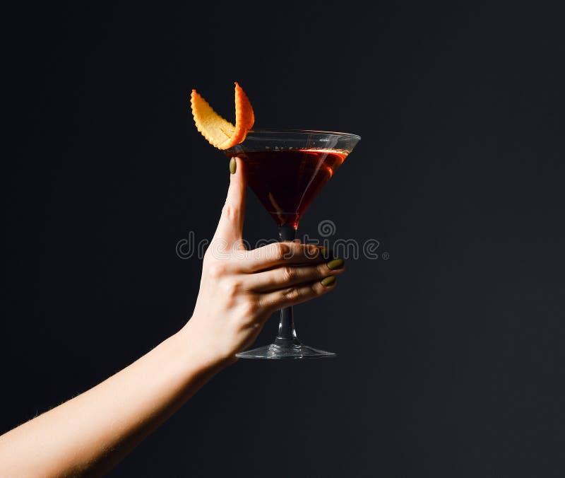 Młodej kobiety ręka z wyśmienicie czerwonym koktajlu napojem z pomarańcze w Martini szkle na zmroku obrazy stock
