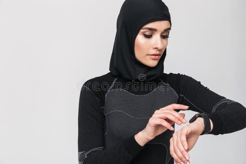 Młodej kobiety sprawności fizycznej zegarka muzułmański używa zegar odizolowywający nad biel ściany tłem fotografia royalty free