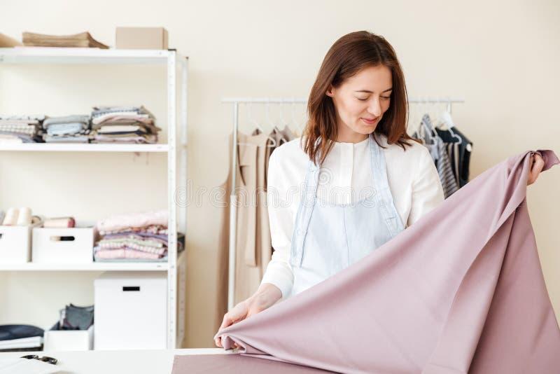 Młodej kobiety szwaczka patrzeje tkaniny obrazy stock